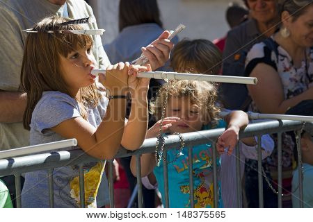 VERONA ITALY - SEPTEMBER 17 2016: Tocati International festival of street games. A little girl is engaging in the game of the blowgun or peashooter (cerbottana in italian) with darts made in curled paper