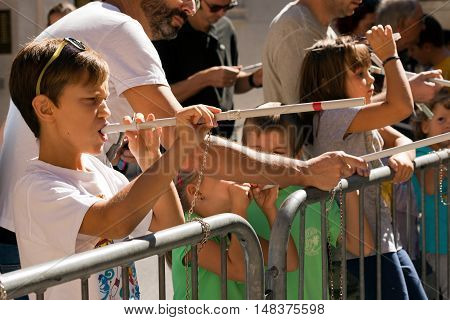 VERONA ITALY - SEPTEMBER 17 2016: Tocati International festival of street games. Some children engage with the game of the blowgun or peashooter (cerbottana in italian) with darts made in curled paper