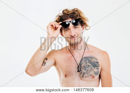 Young smiling curly man taking off suglasses and looking at camera isolated over white background