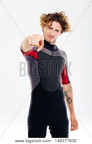 Portrait of a serious concentrated man in diving suit pointing finger at camera over white background