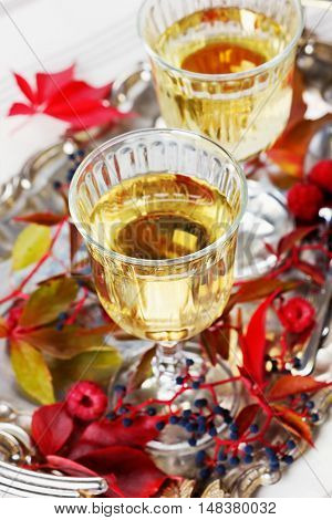Two glasses of white wine on a vintage silver tray decorated with autumn grape leaves and raspberries, romantic picnic. Focus on the top of a glass.
