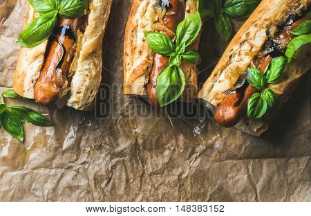 Homemade grilled sausage dogs in baguette with caramelised onion and herbs on baking paper, top view, copy space