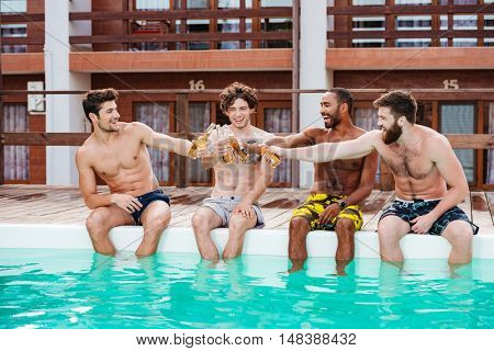 Group of cheerful attractive young men drinking beer and relaxing in swimming pool