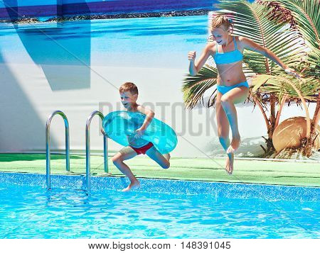 Girl And Boy Jumping Into Resort Pool