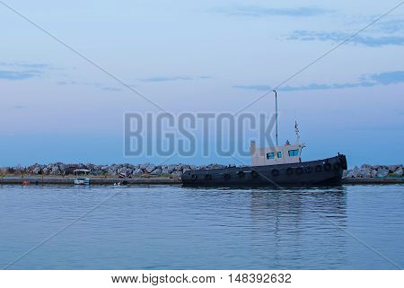 Towboat in the Harbor at Sunrise. Docked Tugboat in the Port at Dawn. Ship in the Sea Bay.