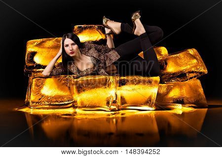 Portrait of a young beautiful sexy woman in a leopard clothes, lying on gold bullion