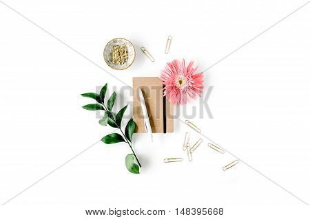 pink gerbera daisy green branch golden clips craft diary and pen on white background. flat lay top view