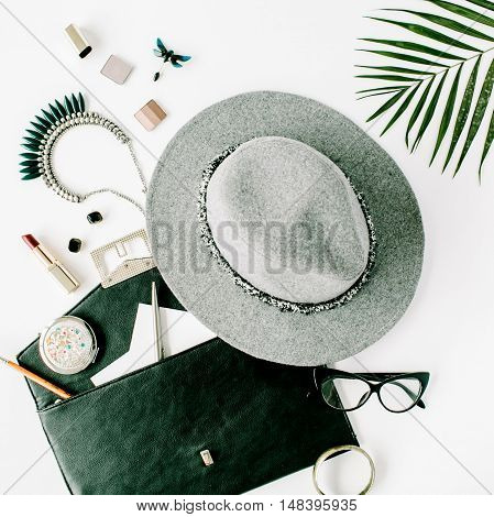 beauty feminine accessories arrangement with palm branch hat purse glasses lipstick and necklace. flat lay top view