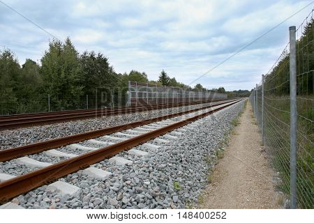 Railway with noise damping wall. Rail Baltica railroad protective fences.