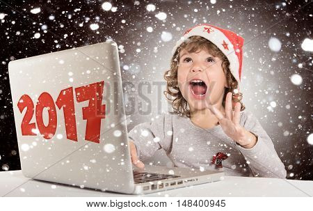 Happy little child with Santa hat and laptop computer celebrate 2017New Year concept