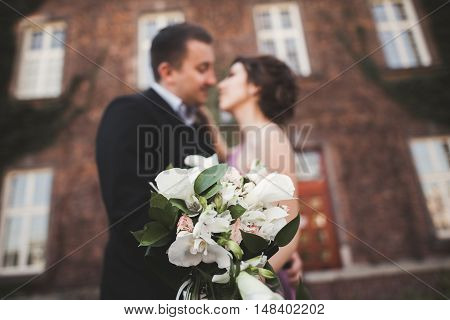 Wedding flowers bouquet with newlywed couple on background.