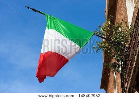 Detail of an Italian flag hanging to a pole on a balcony of Verona with a clear blue sky Veneto Italy