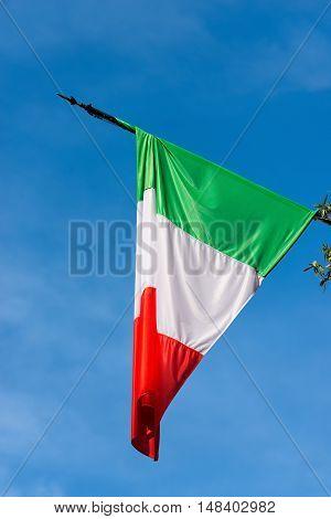 Detail of an national Italian flag with pole on a clear blue sky