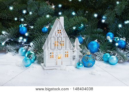 White christmas house glowing with decorations and lights in snow