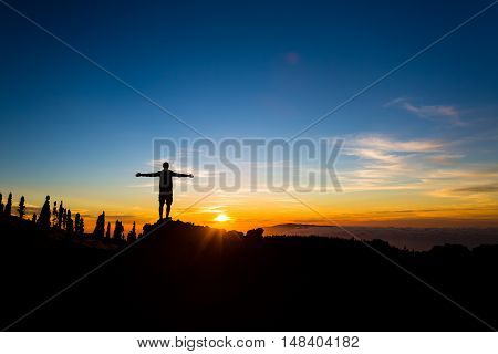 Man with arms outstretched celebrating beautiful inspiring sunset in mountains. Male hiker or climber with hands up enjoy inspirational landscape on rocky trail on Tenerife Canary Islands.