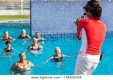 Close up of fitness trainer at senior female aqua gym session. Rear view of instructor with swimmers in outdoor pool background.