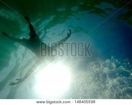 Man drowning in the sea viewed from below underwater