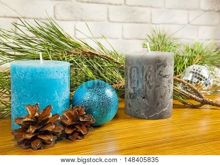 New Year 2017 composition with fir cones and two candles on wooden background