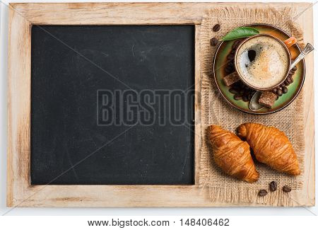 Top view of a cup of coffee with foam and croissants on an old school slate with a wooden frame and blank copyspace on the cleaned chalkboard.