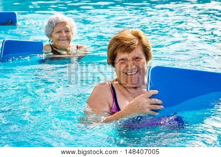 Close up portrait of two senior women doing aqua gym with kicking boards in outdoor swimming pool.
