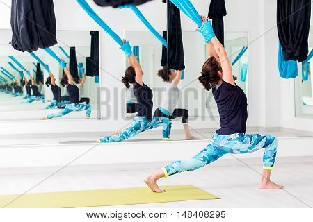 Full length body portrait of young women at aerial yoga session in gym.