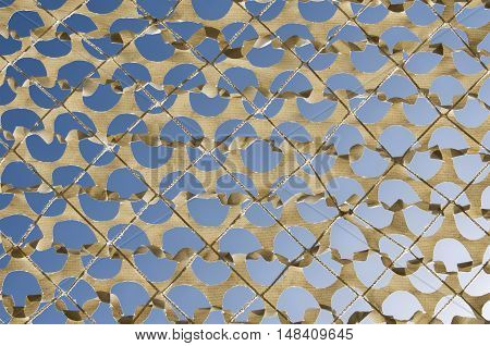 Detail of a beige camouflage grid paper on the bottom blue sky