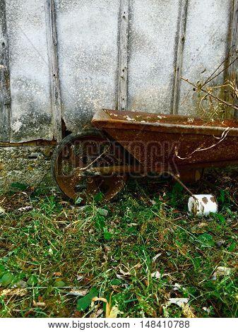 A rusty wheelbarrow near a house in a small village. (Satu Mare, Suceava).