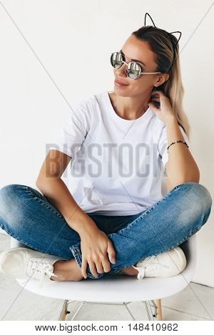 Woman wearing blanc t-shirt, jeans and sneakers sitting on chair, toned photo, front tshirt mockup on model, hipster style