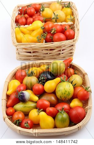 Colorful different kind tomatoes in wooden basket