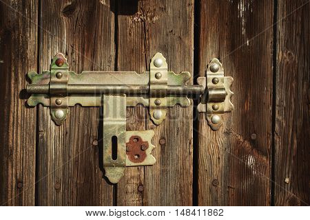 Old lock with latch and keyhole on old wooden door.