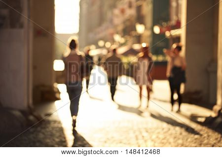 Blurred background of unrecognizable persons rushing through the arch on the touristic street. Evening sunlight forming long shadows.