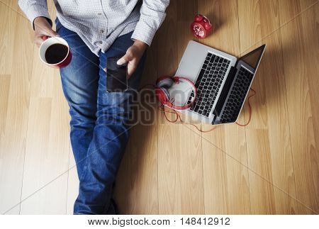Soft photo of man felling comfort use smartphone on the wooden floor with cup of coffee headphone computer laptop and clock Top view point of copyspace relax time.