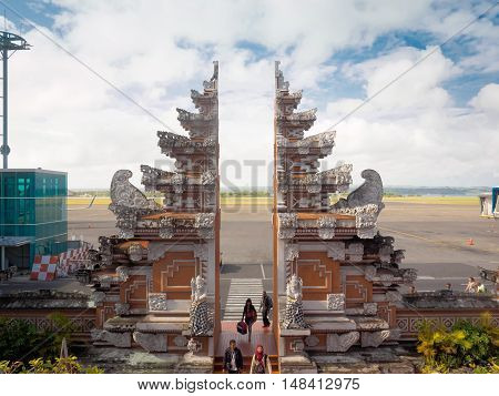 Bali Indonesia - September 18 2016: Flight passengers are walking through Balinese traditional gate from the apron to the arrival terminal of Denpasar International airport also known as Bali Ngurah Rai International Airport Bali island Indonesia.
