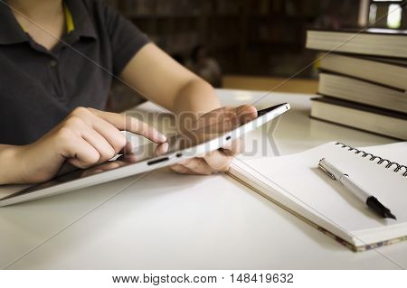 Woman use tablet for working reading communication shopping. Young girl use tablet in library.