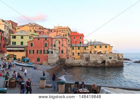 Genoa, Italy - June 25, 2016: Bay with restaurants and bars and Mediterranean Sea in Boccadasse. Boccadasse is an old mariners neighbourhood of Genoa and a tourist attraction.