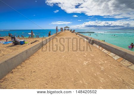 Waikiki, Oahu, Hawaii - August 27, 2016: Waikiki Pier divides Waikiki in: Kuhio Beach has calm waters thanks to a concrete wall and Queens Surf Beach which with its waves are perfect for boogieboard.