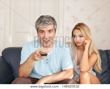 Man switching TV channel on remote control boring wife and marriage dependent