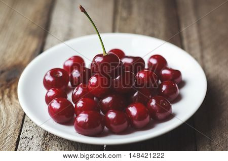 Cherries On Vintage Wooden Table In Plate