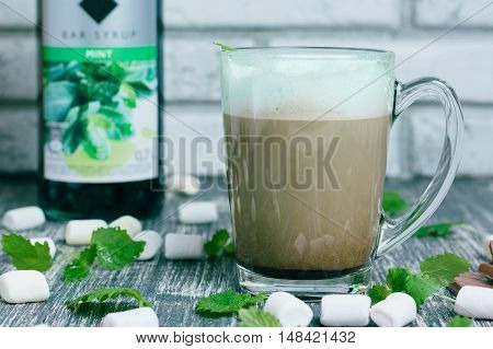Glass of coffee with chocolate cinnamon marshmallow and botle of mint syrup on wooden table