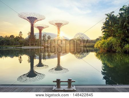 Singapore, Republic of Singapore - May 5, 2016: Supertree grove and Cloud garden greenhouse reflecting in pond at sunrise
