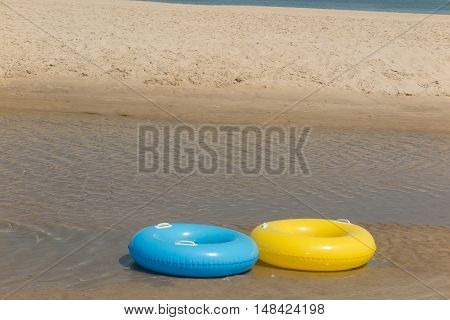 Two Toy Life Preservers Lying On The Beach
