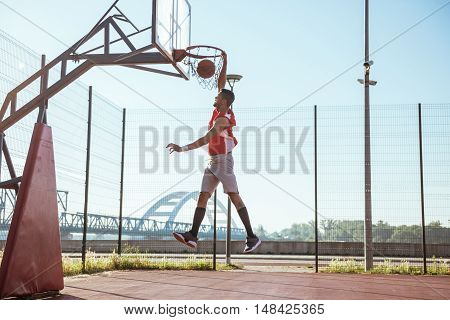 African american basketball player scoring a slam dunk.