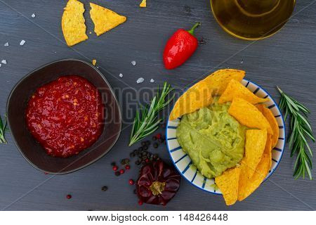 Green guacamole sause with crispy corn chips and pepper salsa sause