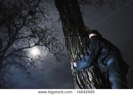 ninja assasin hold katana samurai old martial weapon swordat night with city lights in background