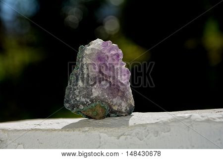 Amethyst on white wall in front of a green background