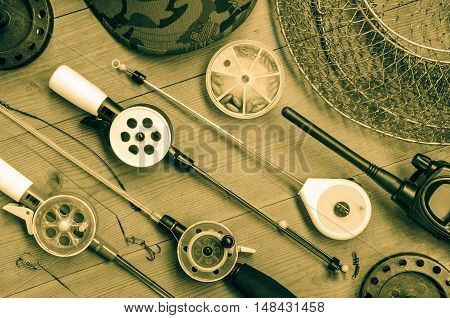 Fishing accessories consisting of tackles radio weights hook net. Wooden background. Outdoor activity and leisure concept. Toned.
