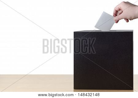 Hand placing folded voting slip into slot in ballot box on light wood table. Isolated on white background.