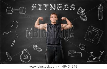 Muscled young man showing his bicep muscles on the background of blackboard with fitness doodles. Healthy lifestyle. Workout and self-improvement.