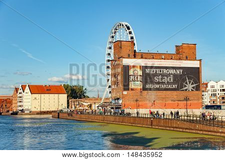 GDANSK, POLAND - SEPTEMBER 18, 2016: People walking on wooden pier in the background big ferris wheel from which you can watch the city skyline.