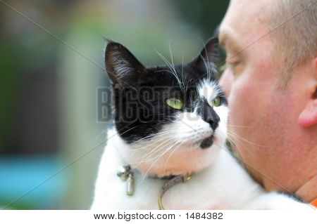 A black and white cat on owners shoulder poster